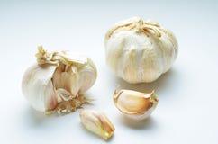Conjunto orgánico y clavos del ajo en el fondo blanco imagenes de archivo
