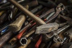 Conjunto sucio de herramientas de la mano en un panel de madera Imagen de archivo