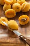 Conjunto y albaricoques cortados en un disco de madera Cuchillo en la pulpa de la fruta Imagen de archivo libre de regalías