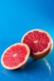 Conjunto y slicend en el medio pomelo en un fondo azul, tiro vertical Imagen de archivo