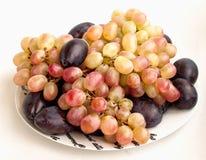 Conjuntos de uvas e de ameixas em uma placa Foto de Stock Royalty Free