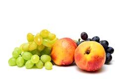 Conjuntos de uvas e de nectarina em um fundo branco Imagem de Stock Royalty Free