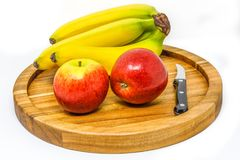 Apples and bananas on a chopping board with a curved blade knife Stock Photos