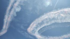 Conluio plano surpreendente com pegada nevoenta no céu azul, trabalho piloto difícil do aeral, elementos do festival aéreo vídeos de arquivo