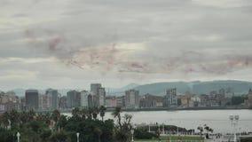 Conluio plano surpreendente com pegada nevoenta vermelha no céu azul, trabalho piloto difícil do aeral, elementos do festival aér video estoque