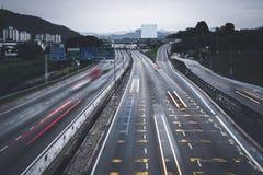 Conmutación ocupada de la gente con los coches usando la carretera entre las ciudades Imagenes de archivo