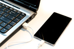 Connec smartphone to notebook. Royalty Free Stock Photo