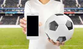 Connect with the football. Cropped image of a young football player holding a soccer ball in one hand and the smartphone in another wearing white tshirt at the Stock Images