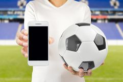 Connect to the football. Cropped image of a young football player holding a soccer ball in one hand and the smartphone in another wearing white tshirt at the Royalty Free Stock Photography