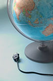 Connect to the world - globe. A globe with detail of the lighting plug on one side Royalty Free Stock Image