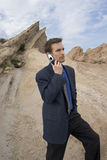 Connected anywhere. Man on cell phone in desert Royalty Free Stock Photo