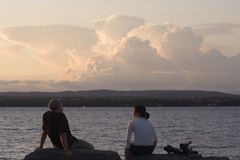 Connected Couple. A couple sitting at the water's edge engaged in conversation, dramatic evening sky Royalty Free Stock Images