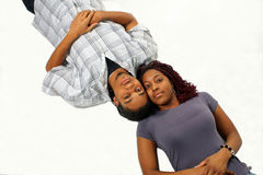 Connected Couple. A metaphorical background with a view of a African American couple lying on a white surface with their faces touching each other stock image