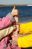 Connected hands of family as symbol of unity. Connected hands of adults and child as symbol of unity of family. Thumb is lifted upwards Stock Photo