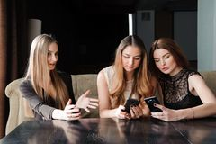 Always connected, internet addiction, young girls in cafe royalty free stock images