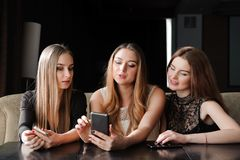 Always connected, internet addiction, young girls in cafe looking at their smartphones, social network concept. royalty free stock photo