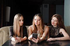 Always connected, internet addiction, young girls in cafe looking at their smartphones, social network concept. royalty free stock photography
