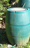 Connected Rain Barrels. Two green plastic rain barrels are connected to capture and store more rain water. When one barrel is full, surplus will flow into the Royalty Free Stock Image