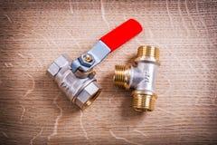 Connecteur de tuyau et robinet à tournant sphérique sur le conseil en bois photographie stock