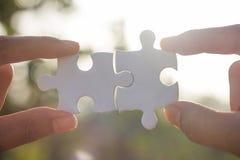 Connecteurs à deux mains de morceau de puzzle denteux, backgroun vert de bokeh photo stock