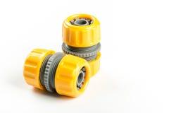 Connecteurs en plastique jaunes de tuyau de l'eau d'isolement au-dessus du fond blanc photos libres de droits