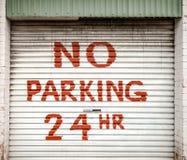 Connectez-vous la porte de garage de ruelle énonçant le STATIONNEMENT INTERDIT 24 heures Photo stock