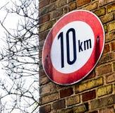 Connectez-vous un mur avec les briques jaunes indiquant la vitesse applicable maximum de 10 kilomètres par heure image stock