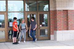 Connecting. Teen girl and guys outside school smiling royalty free stock image