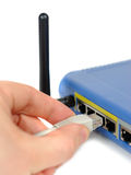 Connecting... Male hand plugging connector into wifi router isolated over white stock image