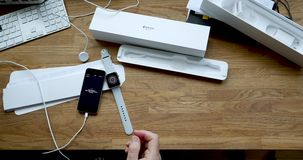 Connecting Apple Watch to iPhone Se smartphone. PARIS, FRANCE - CIRCA 2018: POV man unboxing unpacking latest Apple Watch Series 3 GPS LTE smartwatch wearable stock video footage