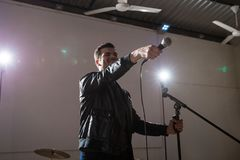 Connecting audience during performance. Rock band lead singer pointing mic towards audience during live concert stock photography