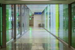 Connecting corridor in green glass hall. Stock Images