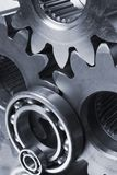 Connecting metal parts. Close-up of cogs, gears and ball-bearings in bluish tint stock image