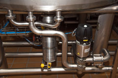 Connecting pipes beneath the big cans on modern plant for production of milk stock images