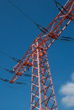 Connecting power. High voltage pylon, red, blue sky, white clouds Royalty Free Stock Photos