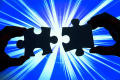 Connecting. Silhouette of two hands connecting pieces of a puzzle on a blue background, with flashing effect royalty free stock image