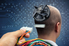 Connecting to cyborg. Hand plugging power cables into the head of cyborg Royalty Free Stock Photography