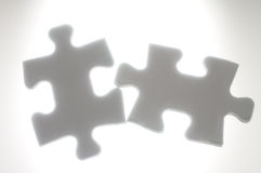 Connecting two puzzle pieces against the light. Stock Photo