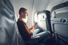 Connection in the airplane. Young man traveler using smart phone during flight and listening music Stock Photography