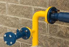 Connection of blue-and-yellow gas pipe, close-up from the street side stock photo