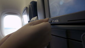 Connection of cell phone and seat monitor in plane. Close-up shot of woman connecting smart phone with seat monitor in plane using USB cable stock video footage