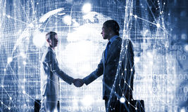 Connection and networking concept . Mixed media. Two businessmen against digital background shaking hands to greet each other. 3D rendering Stock Images