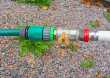 Connection of water pipe and a garden hose with a valve overlap. Plastic gardening hose with threaded Brass fitting connected to water supply valve and pipe stock images