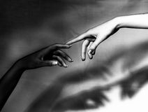 Connections. Black and white hands touch in help for each other. This is a way of seeing the God as female creating black people also meaning that we are one Royalty Free Stock Photos