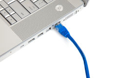 Connectivity - Ethernet Cable in Computer. A blue ethernet cable plugged into an ethernet port on a portable computer with copy space Royalty Free Stock Image