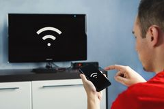 Connectivity between smart tv and smart phone through wifi connection. Control your TV with your smartphone. The wifi icon on the phone screen and the monitor stock image