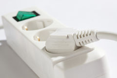 Connectror strip with green switch and plug close up on white background Stock Photography