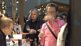 Connoisseurs of alcohol tasting wine during the food fair. HELSINKI, FINLAND - MARCH 18,2018: Connoisseurs of alcohol tasting wine during the Show Gastro stock video footage