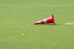 Cono anaranjado que cae en campo de fútbol Fotos de archivo libres de regalías
