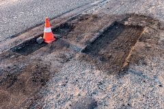 Cono arancio bianco di rischio di traffico sulla riparazione della strada asfaltata fotografia stock libera da diritti